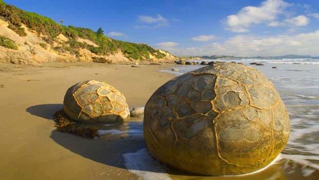Las piedras de Moreaki, parecidas a  enormes huevos de reptil, se formaron en el fondo del océano en Nueva Zelanda y después de siglos de erosión llegaron a la superficie. Foto: BBC Mundo