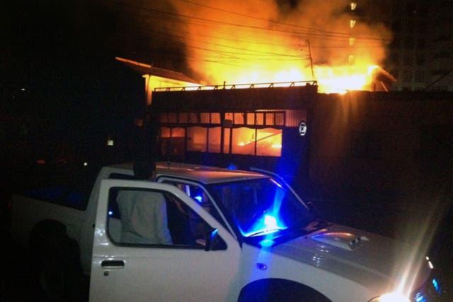 Un hombre mira el restaurant costero que se incendió a raíz del terremoto en la costa de Chile