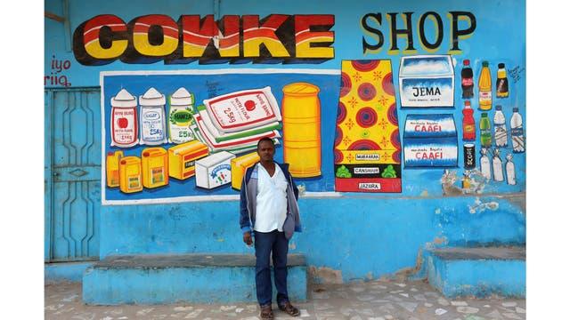 Muawiye Hussein Sidow, también conocido como Shik Shik, se encuentra frente a un mural que pintó en un muro de una tienda