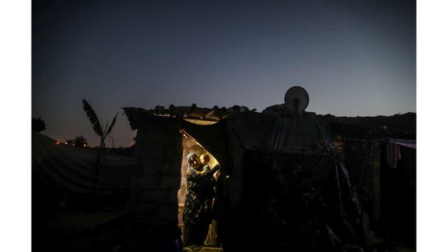 Una mujer con su hijo en brazos sale de su casa iluminada por una linterna durante un corte de luz en Khan Younis, en el sur de la Franja de Gaza