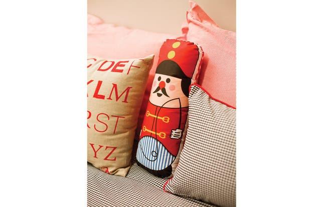 Dúo de almohadones con funda rayada roja y blanca, estampa de letras rojas y cuadrillé negro con cordón rojo (El Círculo de las Vitaminas)..