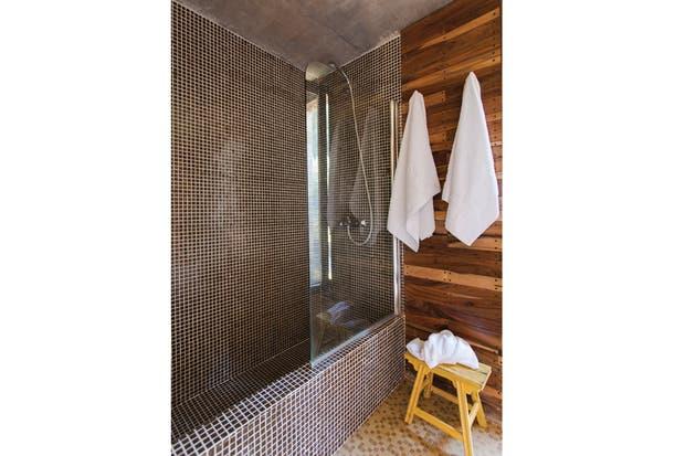 En el sector húmedo, revestimiento de venecitas en tonos tierra y mampara de Blindex para la bañadera, mientras que el resto de las paredes están cubiertas en madera..