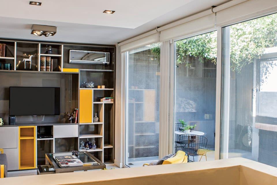 El living está delimitado por un ventanal de piso a techo ($70.000, Alsa Metalúrgica) y por un mueble laqueado en tres tonos con espacio de guardado y nichos para la TV y el aire acondicionado ($95.000).  Foto:Living /Santiago Ciuffo