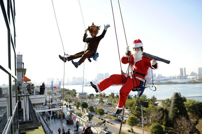 Dos empleados limpia-vidrios festejan en Tokio a cientos de metros de altura. Foto: AFP