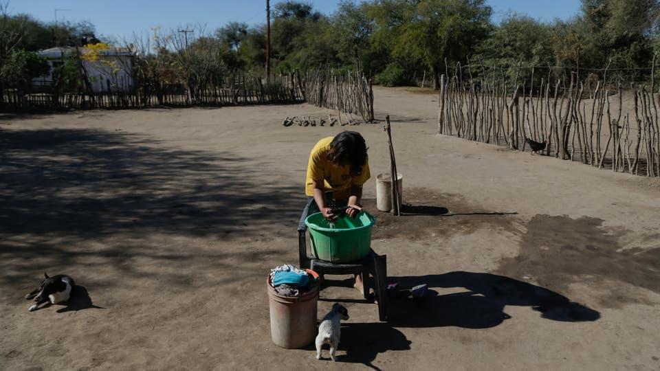 Una jóven discapacitada lava la ropa en un fuentón, el agua potable es escasa en la zona. Foto: LA NACION / Diego Lima