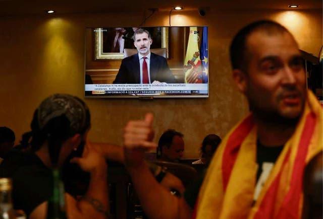 Un grupo de catalanes independentistas escucha el discurso de Felipe en un bar de Barcelona