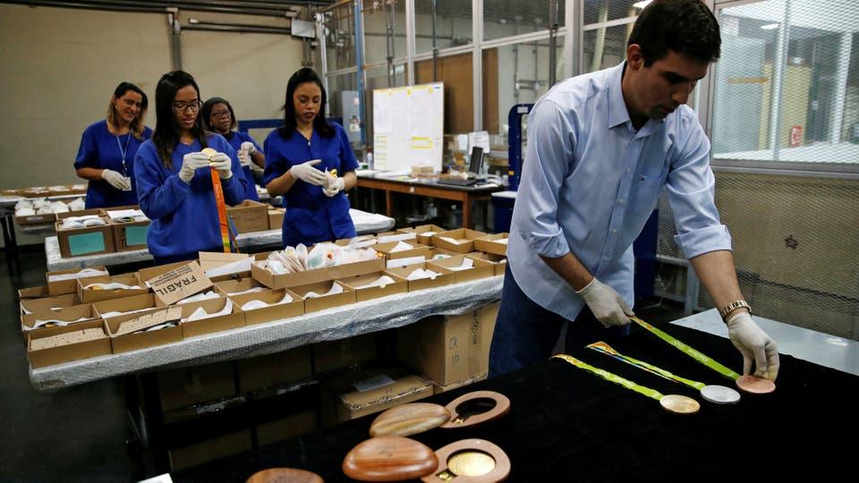 Varias personas forman parte de la fabricación de las medallas. Foto: Reuters / Sergio Moraes