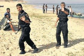 Policías de Hamas revisan una playa de la Franja de Gaza después de un nuevo choque con lanchas y helicópteros israelíes
