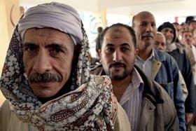 Ciudadanos egipcios hacen cola en una escuela de El Cairo para votar el histórico referéndum