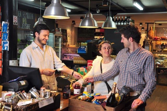 Marcelo Zucchelli paga las compras en The Pick Market; su mujer, Aldana Antonozzi, lleva los gastos del auto