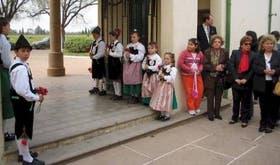 Niños y adultos descendientes de colonos, participando en uno de los actos