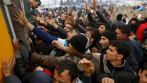 Los refugiados se desesperan ante el reparto de alimentos desde un camión, en un campo cerca de Idomeni