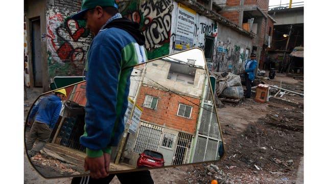 Un hombre lleva un espejo en la Villa 31 en Buenos Aires, Argentina