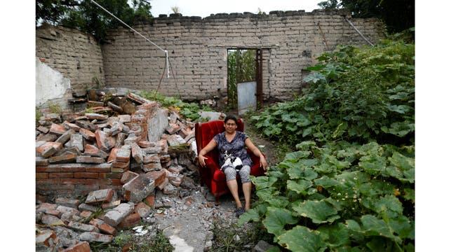 Teresa Luna, una costurera de 49 años, posa con su perro Dokie, junto a parte de su casa que fue gravemente dañada después del terremoto en Chietla