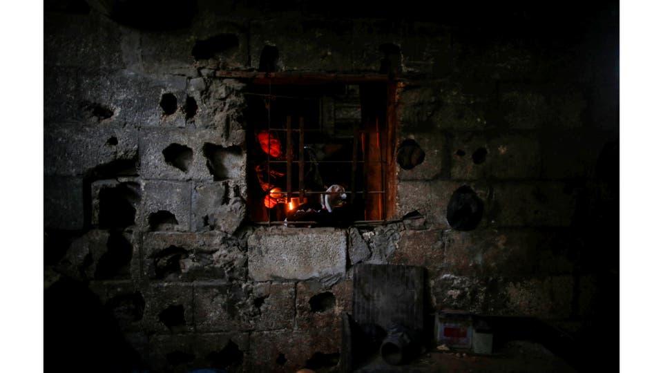 Una mujer se ve a travez de la venta de su cocina mientras prepara la comida a la luz de las velas en Beit Lahiya, al norte de la Franja de Gaza