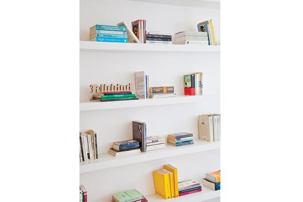 Entre los libros, el cartel 'Felicidad' (Chimi Churri). Otro acierto que aportó luz y claridad fue el reemplazo del viejo piso flotante por microalisado de cemento gris claro, casi blanco ($190 el m2, arquitecta Melina Kleinman).  /Magalí Saberian