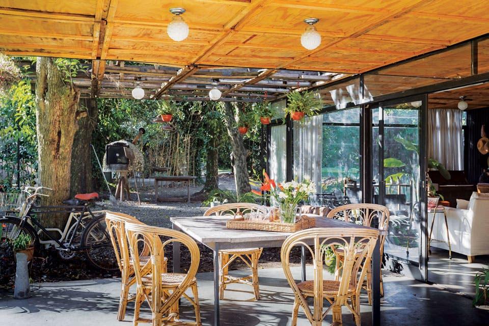 Mesa con base de hierro y tablones rústicos armada por Alejo, sillas Mar del Plata y lámparas 'Glass' de Jaus, la marca que creó Agos Geya, la dueña de casa.  Foto:Living /Daniel Karp