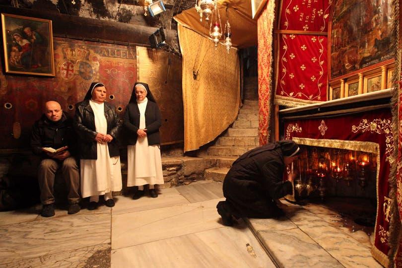 Peregrinos cristianos rezan dentro de la Iglesia de la Natividad (Belén), en el punto donde se presume en nacimiento de Jesucristo. Foto: AP