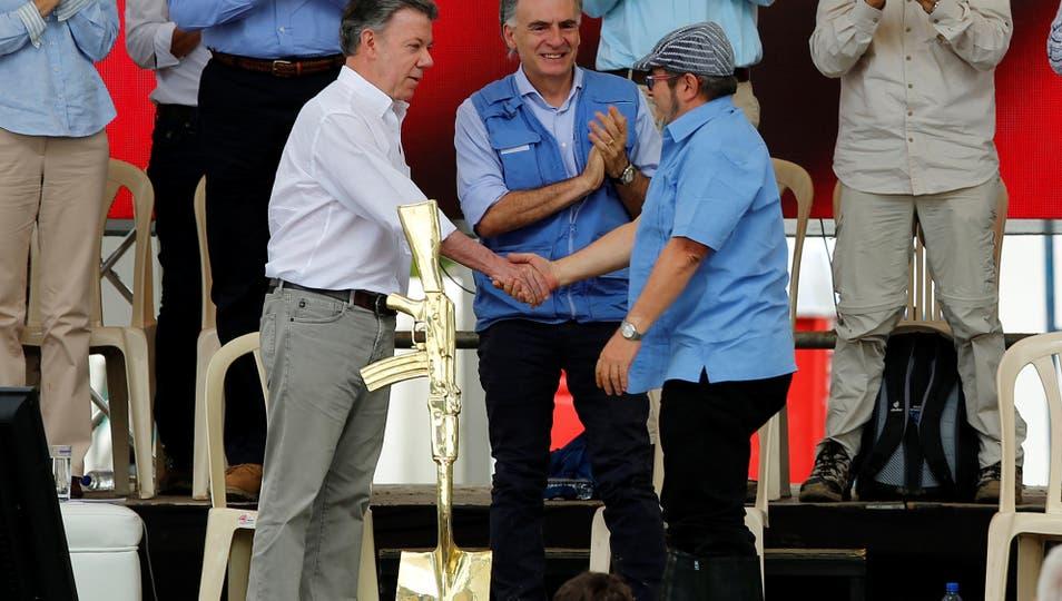 Timochenko, el presidente colombiano Juan Manuel Santos y Jean Arnault, representante especial del secretario general de la ONU para Colombia y jefe de la Misión de las Naciones Unidas en Colombia en el acto de abandono de las armas de la FARC. Foto: Reuters / Jaime Saldarriaga