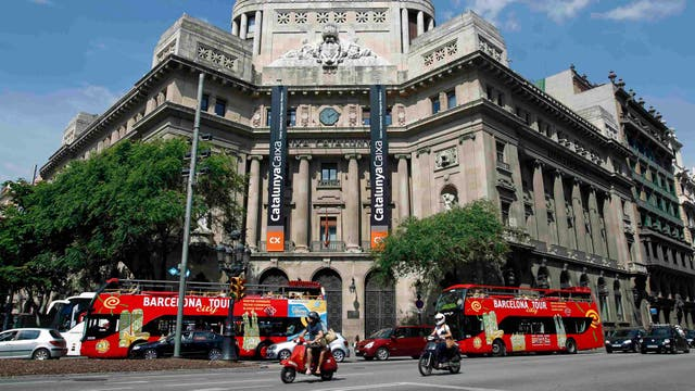 Motociclistas y autobuses turísticos conducir más allá de la sede del banco Caixa Catalunya en el centro de Barcelona.