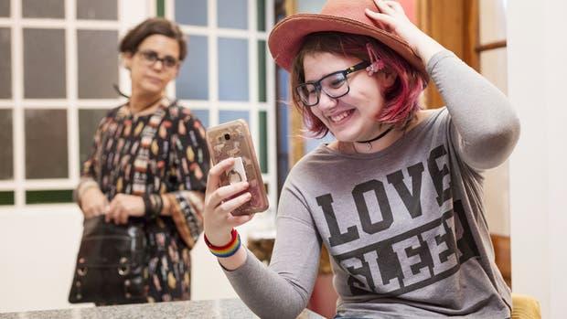 Avril interactúa con su celular ante la atenta mirada de su mamá, Lorena Artayeta