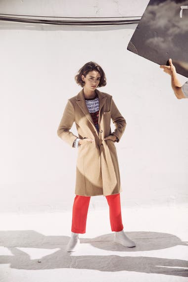 Tapado de lana (Giesso), remera estampada y pantalón recto (Uma), botitas de cuero (Prüne)