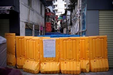 Personas con máscaras faciales caminan en un área residencial bloqueada por barreras en Wuhan, provincia de Hubei, el epicentro del brote de la enfermedad del coronavirus