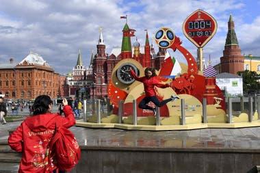 Una voluntario salta para ser fotografiado por una compañero de equipo frente a un reloj que lleva la cuenta regresiva en la Plaza Roja en Moscú