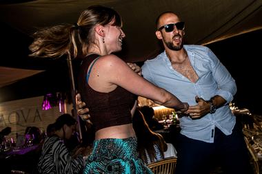 Un hombre y una mujer bailan en la arena en un restaurante al aire libre de una playa en Fregene, cerca de Roma, el 14 de agosto de 2020