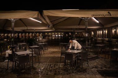 Un camarero cierra la terraza de un bar en la plaza Mayor en el centro de Madrid