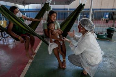 Una trabajadora de la salud atiende a una familia; los médicos se quejan por lo bajo de la falta de insumos mínimos para trabajar