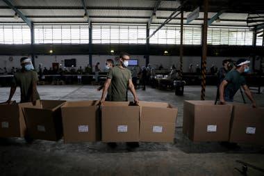 Trabajadores trasladan cajas con votos en Guarenas, Venezuela