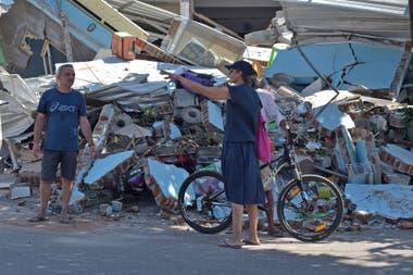 Dos turistas solicitan información a un resiente en medio de un mar de escombros