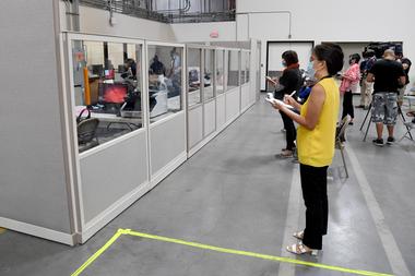 Observadores y miembros de los medios de comunicación observan mientras los trabajadores electorales del condado de Clark escanean las boletas por correo en el Departamento de Elecciones del condado de Clark el 20 de octubre de 2020 en North Las Vegas, Nevada
