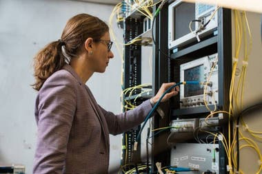 Lídia Galdino, investigadora del University College London, junto a la infraestructura utilizada para probar los algoritmos que buscan asegurar la eficiencia en la transmisión de datos por fibra óptica