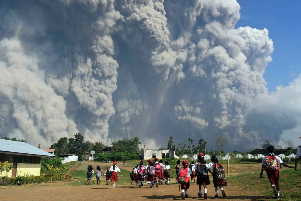 Niños observan la erupción del Monte Sinabung, en Kari, al norte de la isla de Sumatra, en Indonesia
