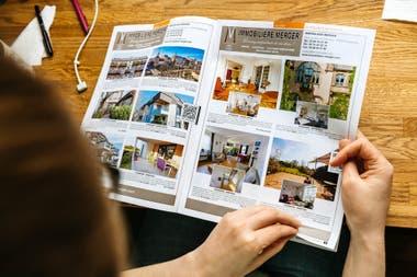 Una mujer lee un catálogo de bienes raíces de casas y departamentos, en París, Francia