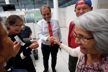 El defensor de la Tercera Edad, Eugenio Semino, junto a jubilados que se acercan a firmar