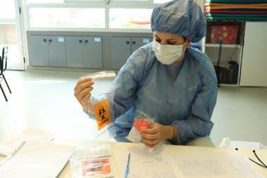 Una agente del plan Detectar en los barrios porteños prepara la muestra de saliva en un frasco estéril para enviarla al laboratorio del Hospital Múñiz