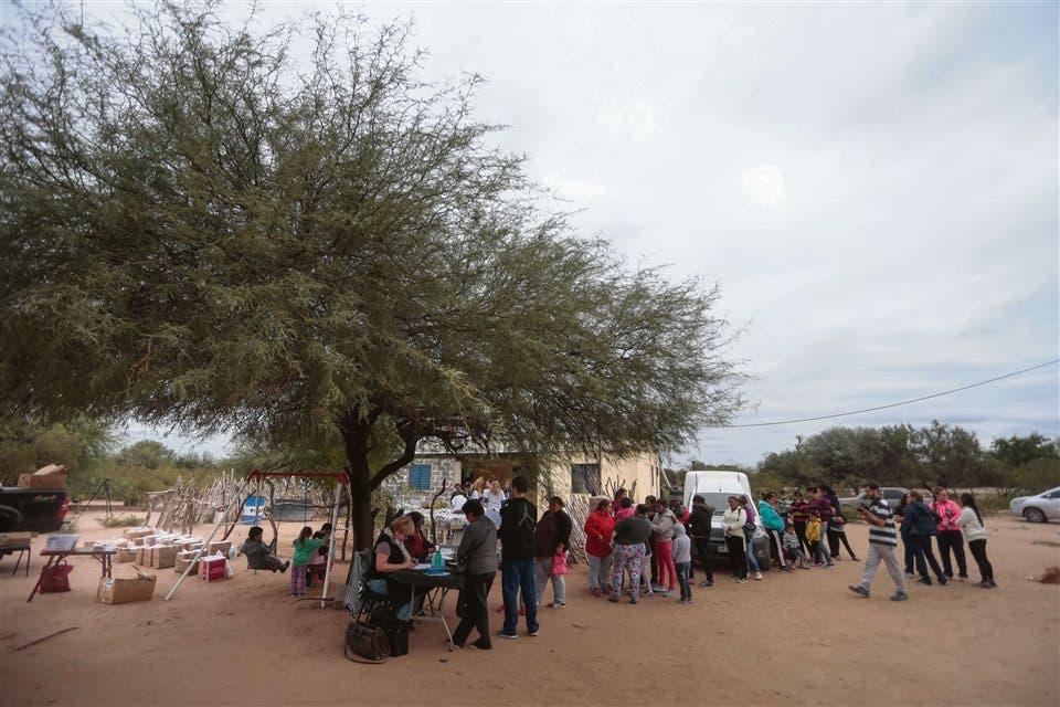 La espera. Los habitantes de Puesto Torrado y otros que se acercan de parajes cercanos hacen fila esperando ser atendidos por los profesionales, mientras unos niños se divierten en las hamacas que donaron los voluntarios