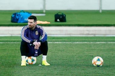 Messi, sentado sobre la pelota en un pasaje de la práctica en Valdebebas (Madrid).