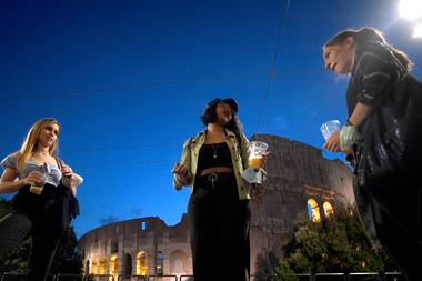 Las personas se reúnen para tomar un aperitivo frente a un bar junto al Coliseo en Roma, el 18 de mayo de 2020