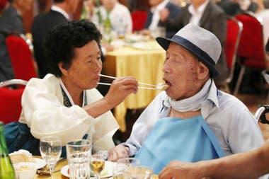 La norcoreana Ahn Jong Sun de 70 años alimenta a su padre surcoreano Ahn Jong-ho de 100 años
