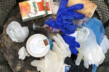 Los guantes y demás suministros médicos se mezclan con los vasos de café en los tachos de Manhattan