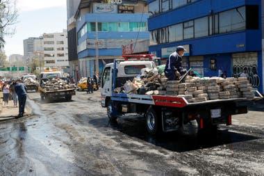 Varios camiones cargados de ladrillos y basura por las calles de la ciudad.