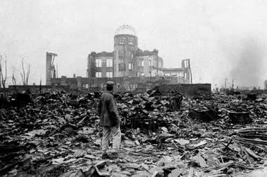 Un hombre camina sobre un mar de escombros y observa el edificio que alguna vez fue una sala de cine en Hiroshima