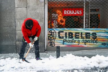 Un hombre quita el hielo de la vereda, en Madrid