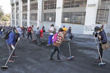 Indígenas, estudiantes voluntarios y residentes locales limpian las calles.