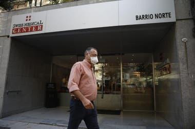 Un hombre con barbijo camina en frente de la clínica de Swiss Medical donde esta internado el hombre de 43 años con coronavirus