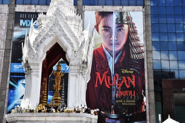 La gente reza en un santuario hindú frente a una publicidad de la película de Disney Mulan afuera de un centro comercial en Bangkok, el 8 de septiembre de 2020